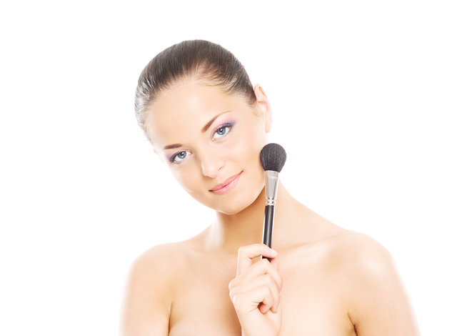 Portrait of a young woman holding a makeup brush