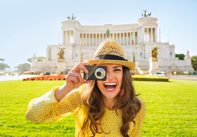 Smiling young woman taking photo on piazza venezia in rome, italy