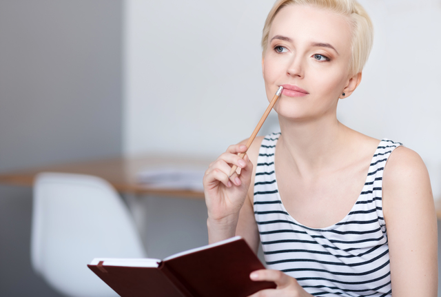 Woman looking aside and holding diary