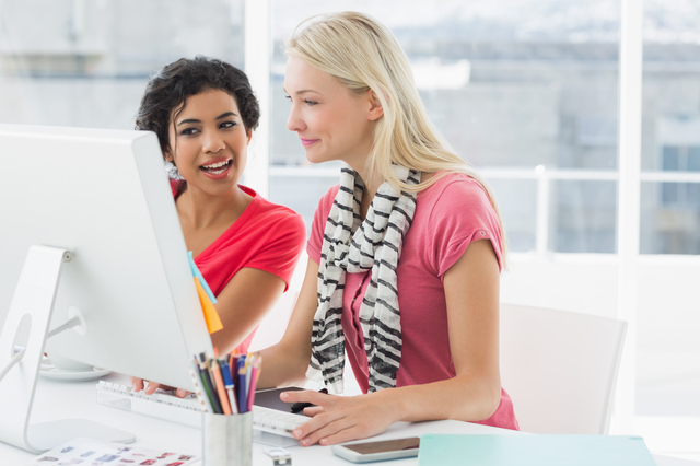 Smiling female business colleagues using computer in a bright office