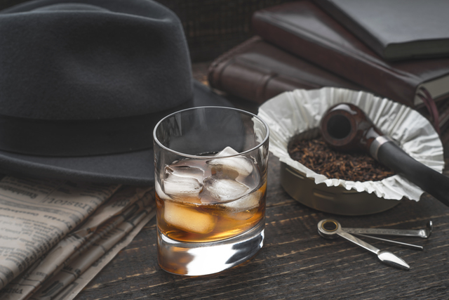 Whiskey with ice , pipe hat and newspaper