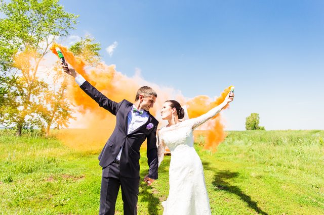 Wedding couple with color smoke in the summer park