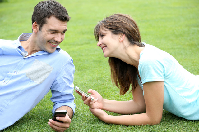 Couple using smartphone laying in public park