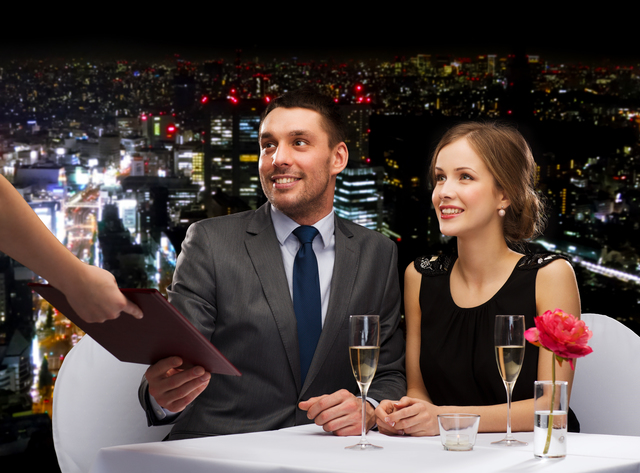waiter giving menu to happy couple at restaurant