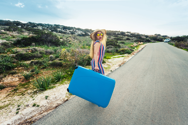 Freedom, travel, vacation and summer concept - Traveler woman walking on the road with suitcases and laughs