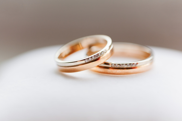 Golden wedding rings with diamonds on white background. Symbol o